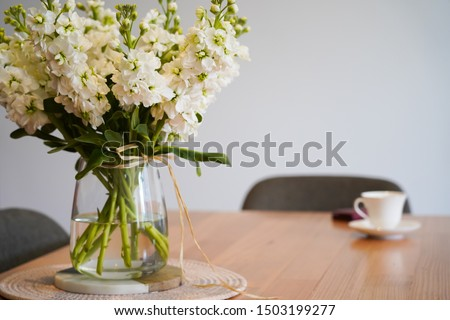 decoration in the table office with full of flowers in the vase and nobody in the room #1503199277