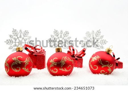 Decoration of red christmas gifts and baubles and snowflakes on snow on white background