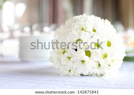 Decoration of the dining table for wedding reception, bouquet of daisies