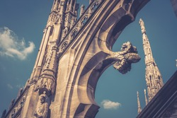Decoration of the Duomo di Milano roof (Milan Cathedral) on sky background, Milan, Italy. Duomo di Milano is largest church in Italy. Historical architecture in Milano. Vintage photo of nice rooftop.
