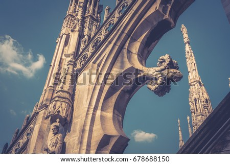 Decoration of the Duomo di Milano roof (Milan Cathedral) on the blue sky background in Milan, Italy. Duomo di Milano is the largest church in Italy. Historical architecture in Milano. Vintage photo.