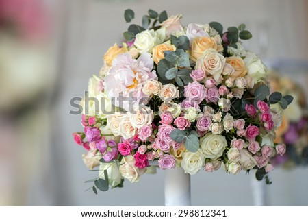 Decoration of wedding posy of fresh beautiful flowers of roses and peony white pink violet purple yellow lilac and orange colours in slim vase indoor, horizontal picture