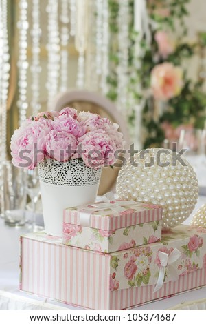 decoration of wedding table. flowers in vase with gift boxes that stand on each other and ball