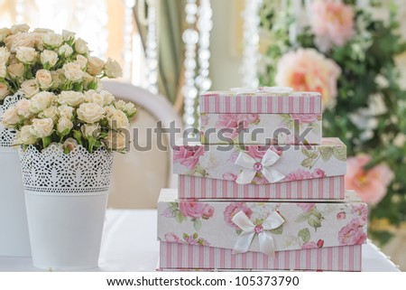 decoration of wedding table. Roses in vase with gift boxes that stand on each other