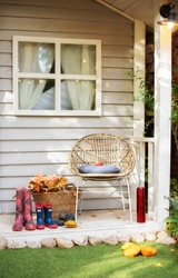 Decorations in autumn patio for relax. Stylish fall decor on front veranda home. Autumn wooden porch home. Cozy Autumn terrace with chair, plaid, rubber boots, baskets with chrysanthemums and pumpkins