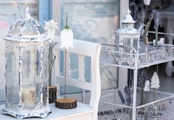 Decorative and creative ornamental interior and exterior floral design elements, vintage glass candle holders placed on a stylish white bench, wedding accessories
