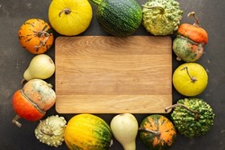 Decorative and edible pumpkins on a green background, rectangular cutting board in the middle of the background, top view, autumn background, copy space