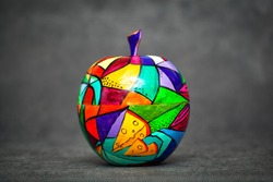 Decorative apple, made of wood and painted by hand paints on abstract black background. contemporary art, modern art