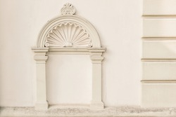 Decorative arch and semi vault above niche with classic pillars. Architectural stucco detail of old European buildingin Prague. Elegant masonry facade decor in beige color. No people, front view.