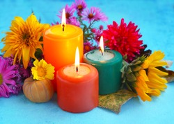 Decorative autumn candles burning and flowers