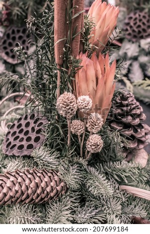 Decorative autumnal flower arrangement with cones and spruce twigs in oranges and green, vertical image.