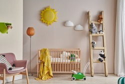 Decorative baby room, wooden cradle, child toy, stairs and pink chair with cabinet furniture.