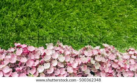 Decorative background artificial pink  flowers on a grass wall. #500362348