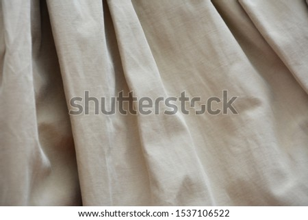 Decorative background. Fabric background. Beige fabric. Folds on the fabric. #1537106522