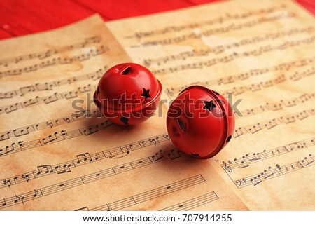 Decorative bells on music sheets. Christmas songs concept #707914255