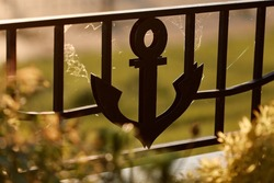 Decorative black metal anchor on the fence of the river port