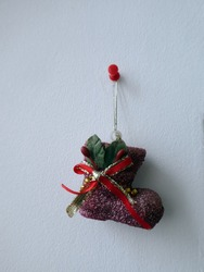 Decorative boot with red ribbon hanging on the wall