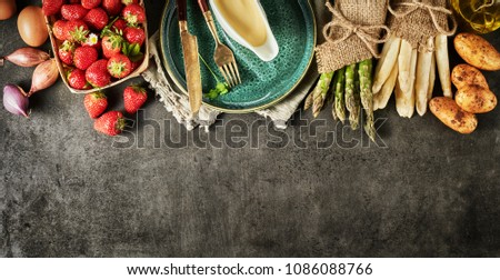 Decorative border of fresh spring fruit and vegetables with green and white asparagus, potatoes, shallots, strawberries and gourmet Hollandaise sauce over textured slate with copy space #1086088766