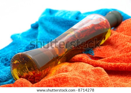 decorative bottle with olive oil and spices between colorful scarves