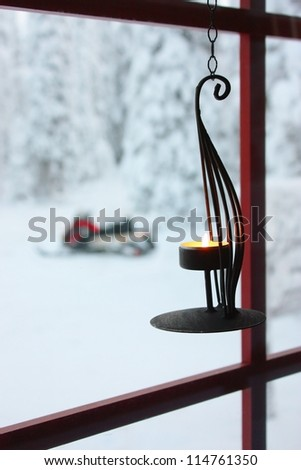 Decorative candle holder with burning candle hanging on window to the snowy winter yard with trees covered in snow and snowmobile
