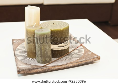 Decorative candles and incense stick on the tray on the white table
