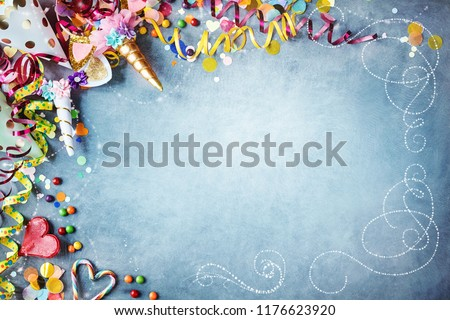 Decorative carnival party background with colorful hats, streamers, unicorn costumes, candy, confetti and hearts as a border against a textured blue background with vignette and copy space Foto stock ©