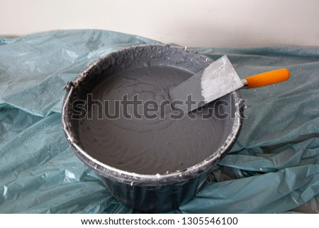 Decorative cement plaster and a trowel in a construction bucket ready for plastering #1305546100