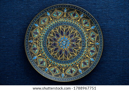 Photo of  Decorative ceramic plate with black, blue and golden colors, painted plate on background of fabric, closeup, top view. Decorative porcelain plate painted with acrylic paints, handwork, dot painting