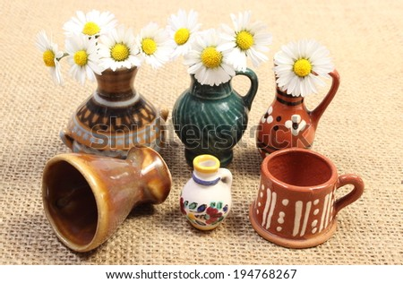 Decorative ceramic vases standing on jute canvas and fresh white daisies in glass vases