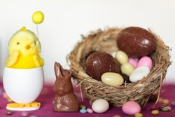 Decorative chik, chocolate bunny missing a bite and bird nest with chocolate eggs and sweet almonds against white background