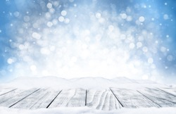 Decorative Christmas background with bokeh lights, snowflakes and empty old wooden table. Christmas and Happy New Year blue background with snowflake. Winter landscape with falling snow.