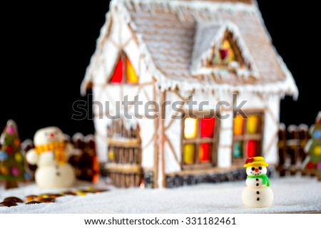 Decorative Christmas  gingerbread house with lights inside on black background
