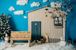 Decorative Christmas studio with a house with blue door, wooden bench and skis, snowman, fake clouds and snow