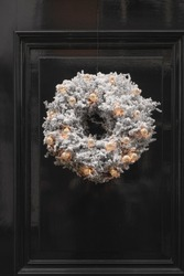 Decorative Christmas wreath covered in artificial snow with illuminated gold colored baubles attached to a green door of a house in Deventer in The Netherlands