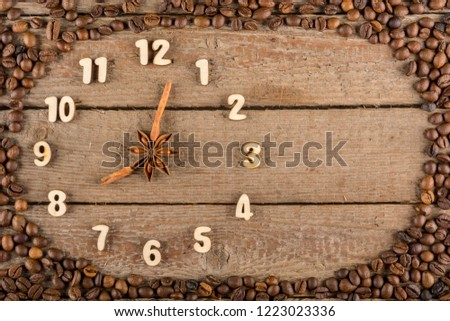 Decorative clock with wooden numerals and arrows made of cinnamon sticks, showing 8 o'clock, on a wooden background and a frame of coffee beans. Kitchen, advertising, banner, Copy space, flatly. #1223023336