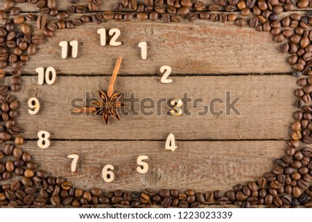 Decorative clock with wooden numerals and arrows made of cinnamon sticks, showing 9 o'clock, on a wooden background and a frame of coffee beans. Kitchen, advertising, banner, Copy space, flatly. #1223023339