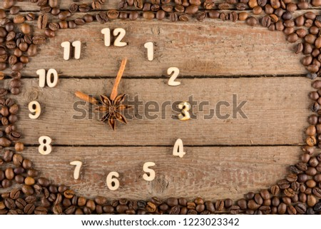 Decorative clock with wooden numerals and arrows made of cinnamon sticks, showing 10 o'clock, on a wooden background and a frame of coffee beans. Kitchen, advertising, banner, Copy space, flatly. #1223023342