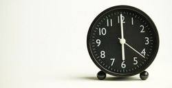 Decorative close-up black analog alarm clock for 6 o'clock or 18 o'clock, separate white background with copy space.