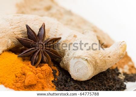 Decorative close-up image of spices like ginger, star anise, curcuma and black tea.