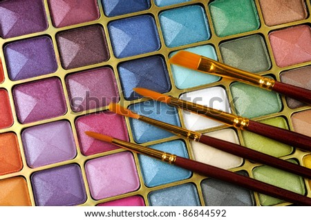 Decorative colorful eyeshadow and brushes , close up shot - stock photo