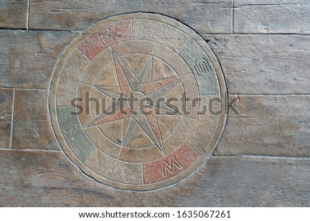 Decorative compass directional arrows indicating north, south, east and west and intermediate directions on the stone ground, for getting direction. Flat lay, top view with copy space.