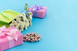 Decorative composition boxes with gifts flowers women's jewelry shopping holiday blue background. Festive poster copy space