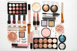 Decorative cosmetics and makeup brushes on a white background, top view