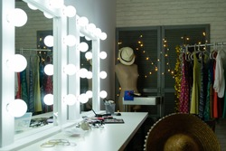 Decorative cosmetics and tools on dressing table with bright mirror in makeup room. empty nobody backstage straw hat on dummy. lights hanging on wall door beside clothing rack indoors interior.