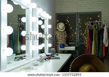Decorative cosmetics and tools on dressing table with bright mirror in makeup room. empty nobody backstage straw hat on dummy. lights hanging on wall door beside clothing rack indoors interior. #1359732893