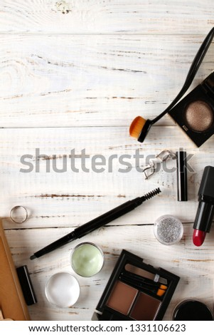 Decorative cosmetics lipstick, eye shadow, pencil and other cosmetics on a wooden white background. #1331106623