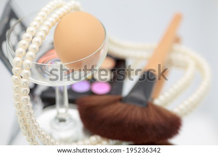 Decorative cosmetics makeup. pink,yellow,blue, brush pearl egg cosmetics on table, violet