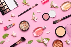 Decorative cosmetics mascara powder lipstick eyeshadow blush balls makeup brush perfume blooming spring branches on pink background top view Flat lay. Beauty blogger concept. Fashion background