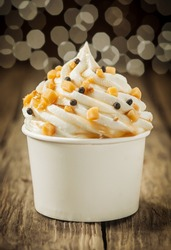 Decorative creamy party vanilla ice cream sundae twirled in a takeaway plastic tub and sprinkled with chocolate pearls and nuts with a background bokeh of party lights