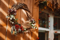 Decorative design window on the terrace. autumn wreath and pumpkins vintage old chest of drawers on wooden rustic background. autumn composition and recreation area sun ray